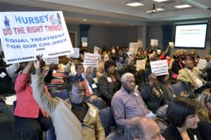 Parents at the Charleston School Board holding up signs asking for Montessori and traditional tracks at Hursey Elemetary School. Photo credit: Tolbert Smalls Jr., Charleston Chronicle